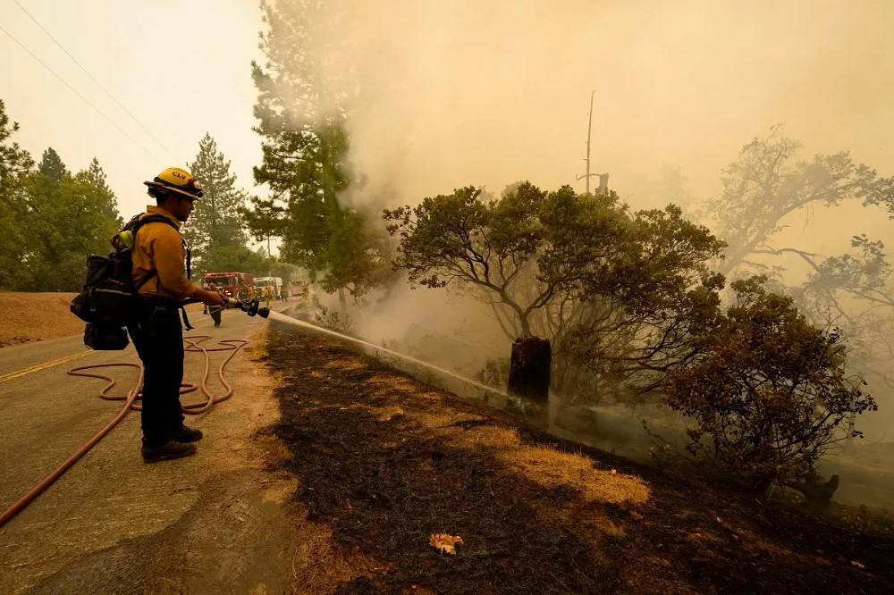 Rick Archuleta of the Clovis Fire Department hoses down hotspots left behind by the Creek Fire, Sept. 8, 2020, in Tollhouse, Calif. (AP)